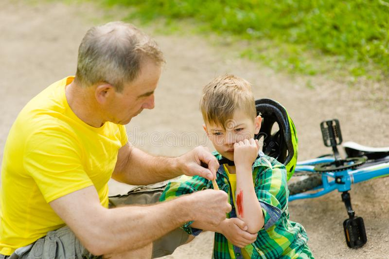Grootvader die pleister op de verwonding van de jonge jongen zetten die van zijn fiets viel stock afbeelding