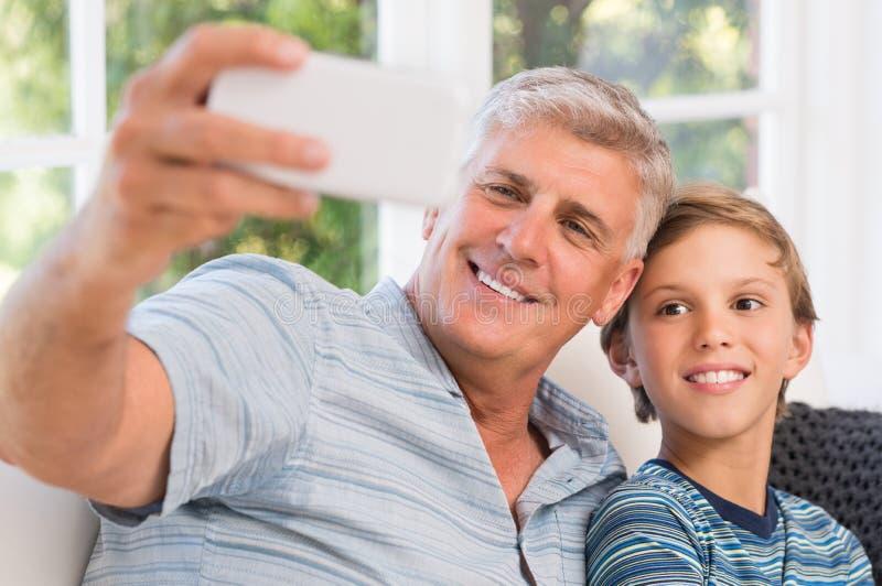 Grootvader die selfie met kleinzoon nemen stock afbeeldingen