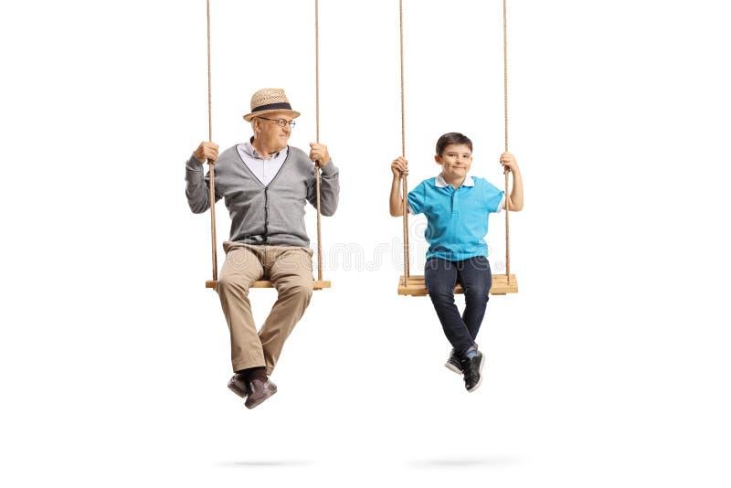Grootvader die zijn kleinzoon bekijken en op houten schommeling zitten stock fotografie