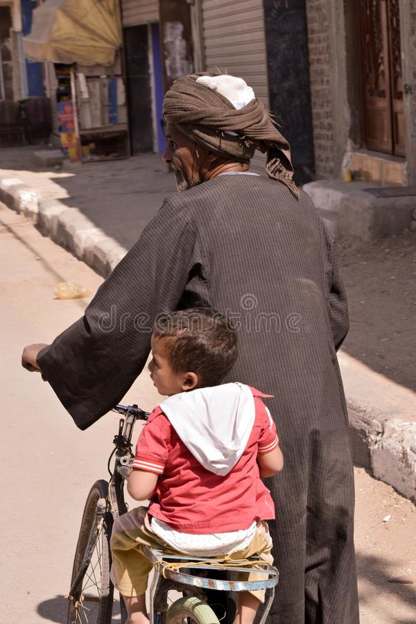 Grootvader drijfkleinzoon op fiets stock fotografie