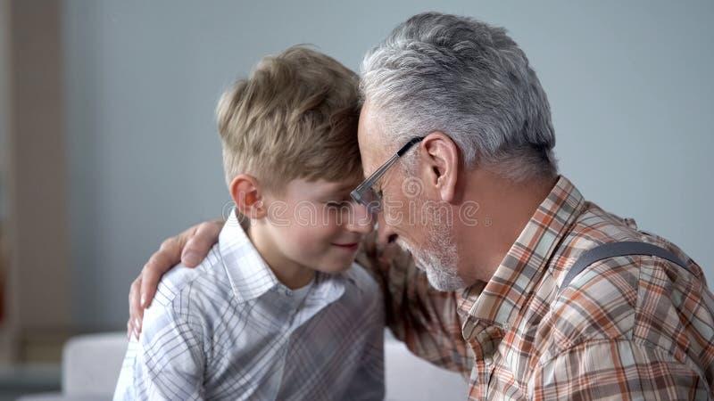 Grootvader en jongens leunende voorhoofden samen, bezoek op weekend, bejaarde zorg stock afbeeldingen