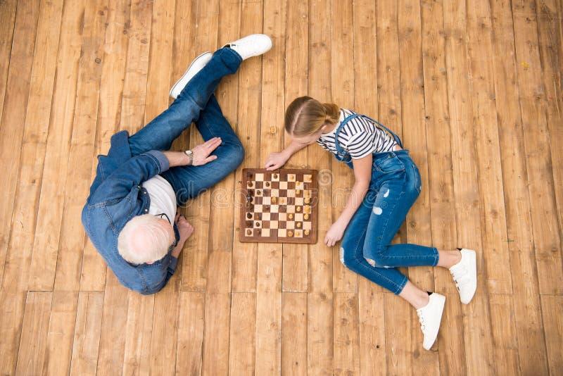 Grootvader en kleindochter het spelen schaak op hardhoutvloer royalty-vrije stock fotografie