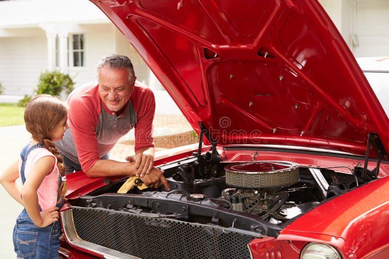 Grootvader en Kleindochter het Werk aangaande Herstelde Klassieke Auto royalty-vrije stock fotografie
