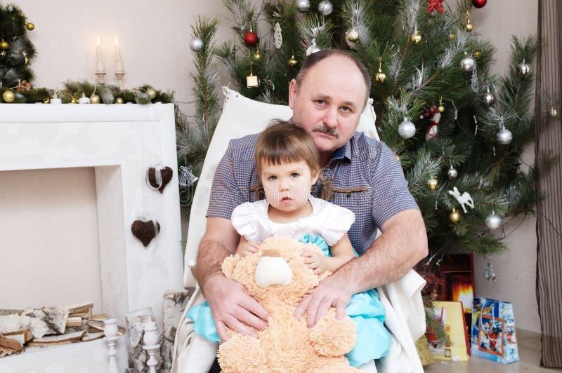 Grootvader en kleindochterportret in Kerstmisbinnenland Meisjezitting achter oudere vader met Teddybeer royalty-vrije stock fotografie