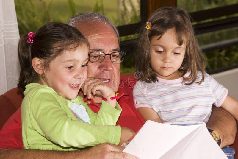 Grootvader en kleindochters die samen lezen