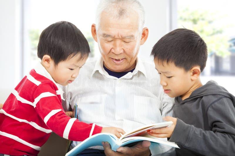 Grootvader en kleinkinderen die een boek lezen stock fotografie