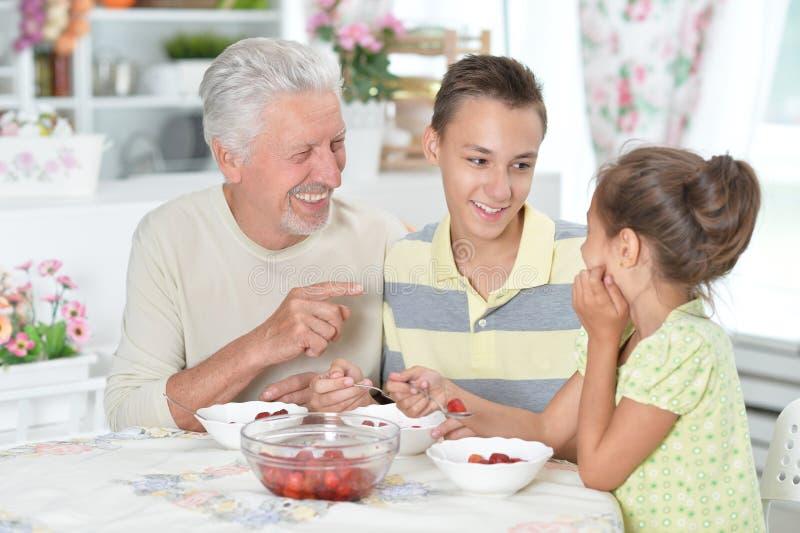 Grootvader en kleinkinderen die verse aardbeien eten bij kitch royalty-vrije stock foto