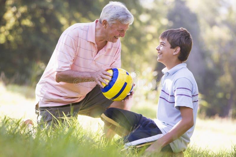 Grootvader en kleinzoon bij een park met een bal stock afbeeldingen