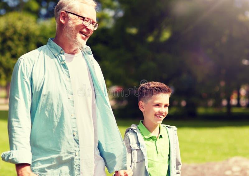 Grootvader en kleinzoon die bij de zomerpark lopen royalty-vrije stock afbeeldingen