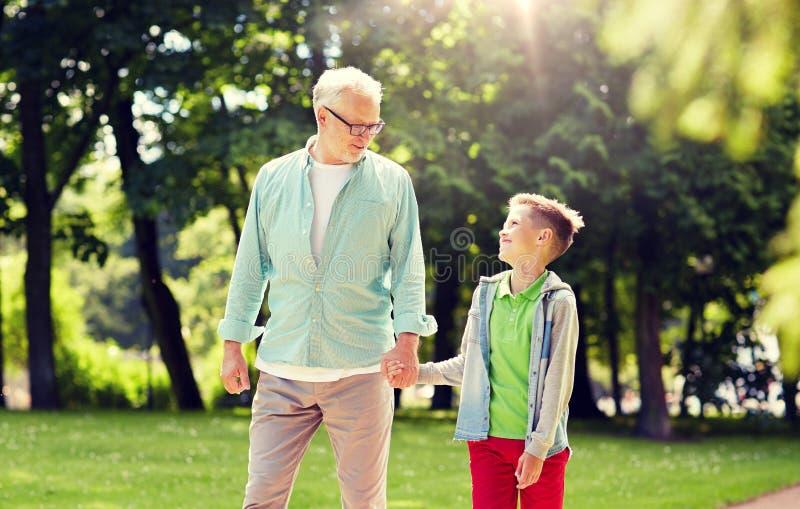 Grootvader en kleinzoon die bij de zomerpark lopen royalty-vrije stock foto