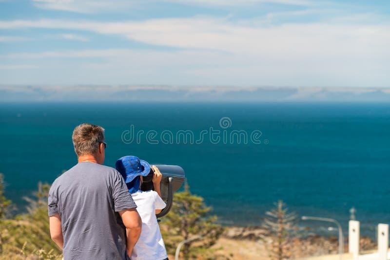 Grootvader en kleinzoon die de kust van het Kangoeroeeiland waarnemen door openlucht binoculair stock foto