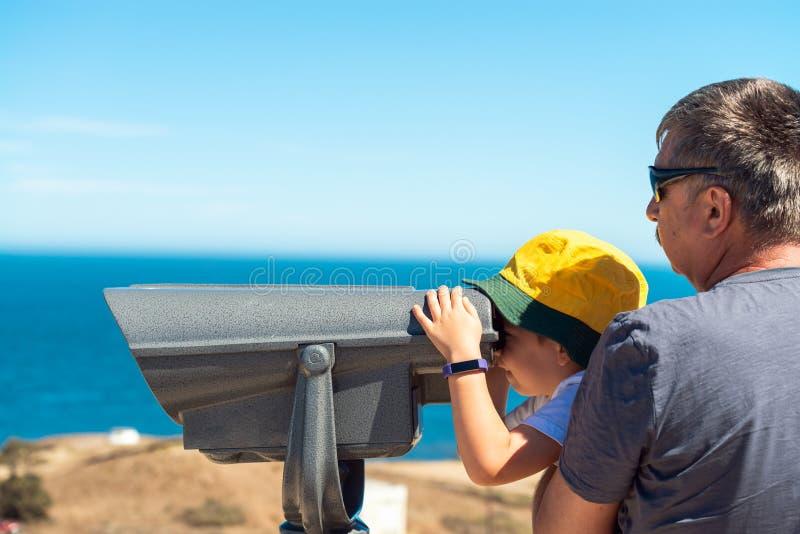Grootvader en kleinzoon die de kust van het Kangoeroeeiland waarnemen door openlucht binoculair royalty-vrije stock afbeelding