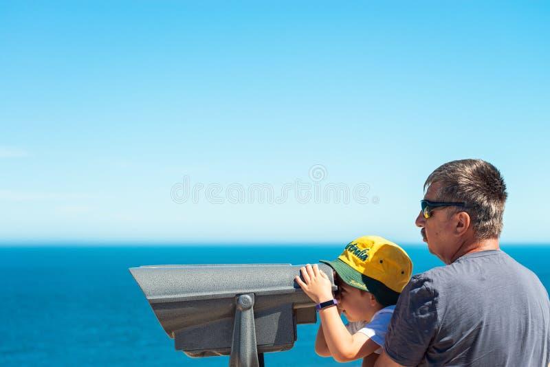 Grootvader en kleinzoon die de kust van het Kangoeroeeiland waarnemen door openlucht binoculair stock foto's