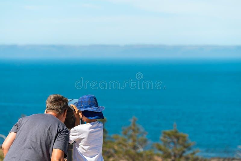 Grootvader en kleinzoon die de kust van het Kangoeroeeiland waarnemen door openlucht binoculair royalty-vrije stock foto's