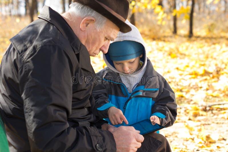 Grootvader en kleinzoon die een tablet-PC delen royalty-vrije stock fotografie