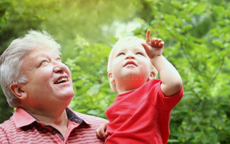 Grootvader en kleinzoon die op bovenkant en glimlach kijken Leuke peuterjongen met zijn grootvader in de zomerpark royalty-vrije stock fotografie