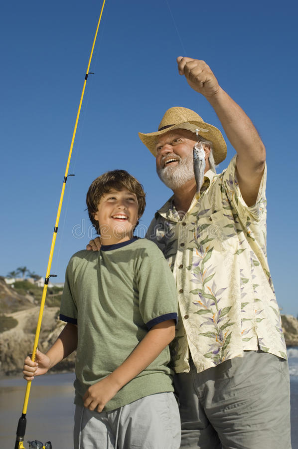 Grootvader en Kleinzoon die op Strand vissen royalty-vrije stock foto