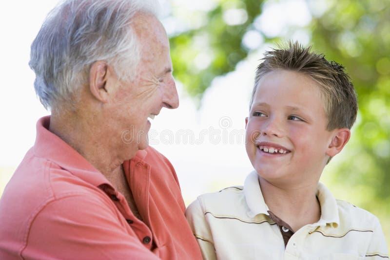 Grootvader en kleinzoon die in openlucht glimlachen. royalty-vrije stock afbeelding