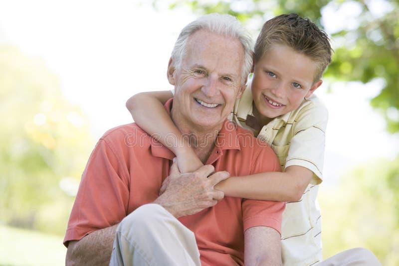Grootvader en kleinzoon die in openlucht glimlachen royalty-vrije stock fotografie