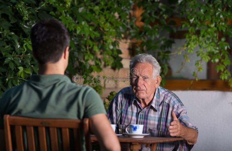 Grootvader en kleinzoon die in tuin spreken royalty-vrije stock foto's