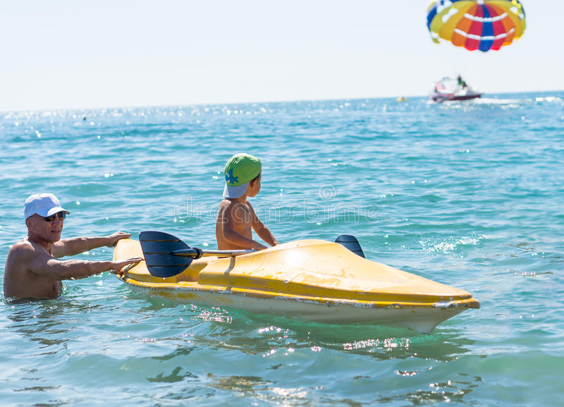 Grootvader en kleinzoon die weinig babyjongen in het groene honkbal GLB kayaking glimlachen bij tropische oceaanoverzees in de da royalty-vrije stock foto's