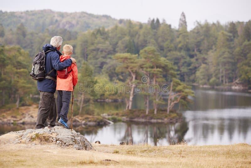 Grootvader en kleinzoon die zich op een rots bevinden die de mening van een meer bewonderen, achtermening, Meerdistrict, het UK royalty-vrije stock foto's