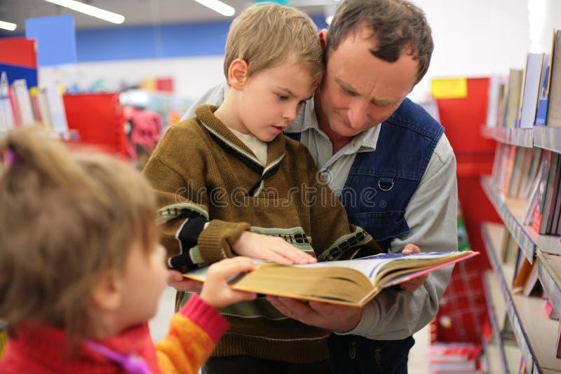 Grootvader en kleinzoon en meisje gelezen boek stock fotografie