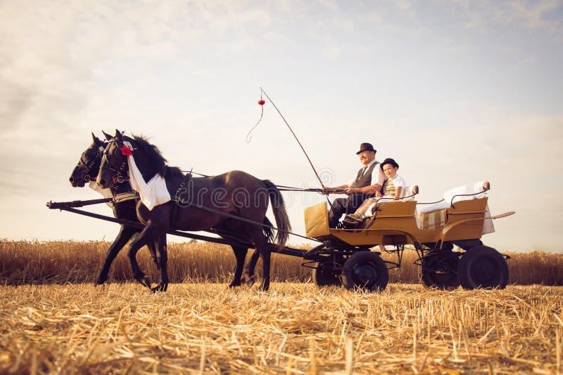 Grootvader en kleinzoon het rideing in vervoer die traditioneel kostuum in Vojvodina, Servië dragen