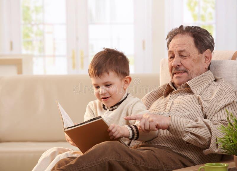 Grootvader en kleinzoon samen thuis stock afbeelding
