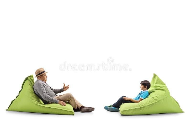 Grootvader en kleinzoonzitting op kinderspel en het spreken stock afbeelding