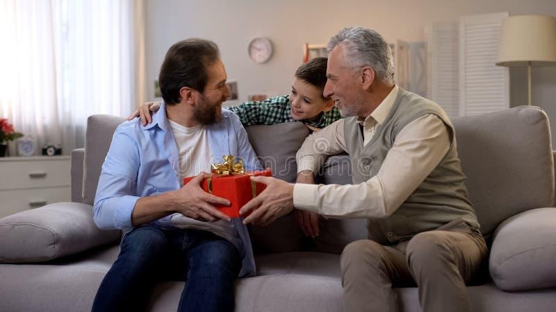 Grootvader en schooljongen die de mens op middelbare leeftijd gelukwensen en rode giftdoos geven royalty-vrije stock afbeeldingen