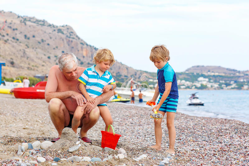 Grootvader en twee kleine jong geitjejongens op oceaanstrand royalty-vrije stock afbeelding