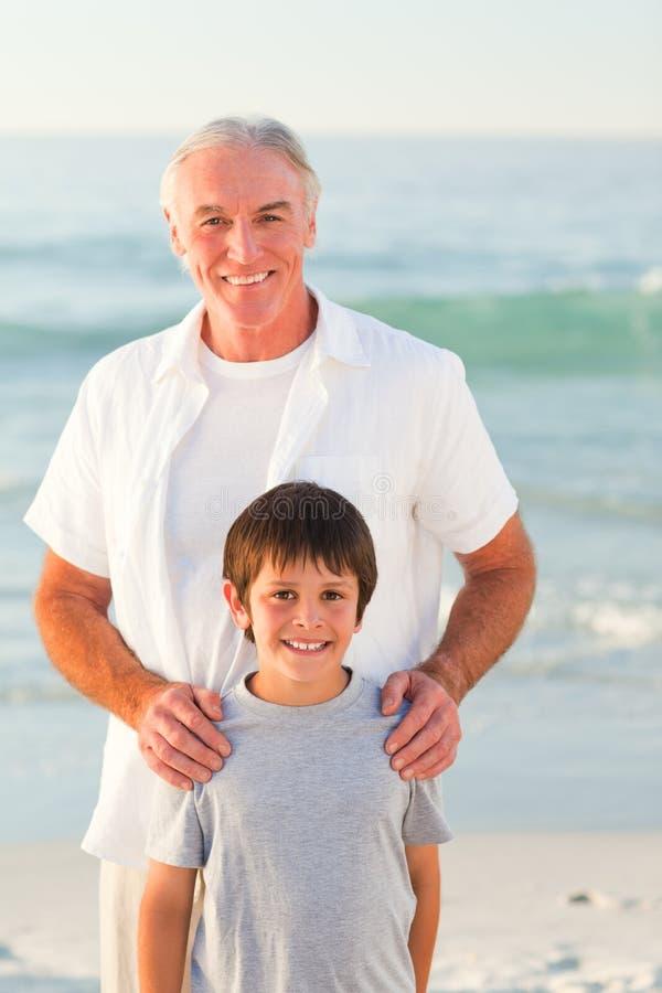 Grootvader en zijn kleinzoon bij het strand stock afbeelding