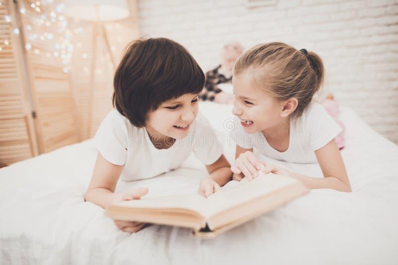 Grootvader, kleinzoon en kleindochter thuis De kinderen lezen boek terwijl de opa slaapt stock foto's