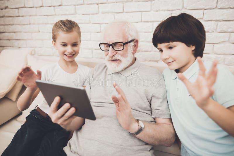 Grootvader, kleinzoon en kleindochter thuis De opa en de kinderen nemen selfie royalty-vrije stock afbeelding