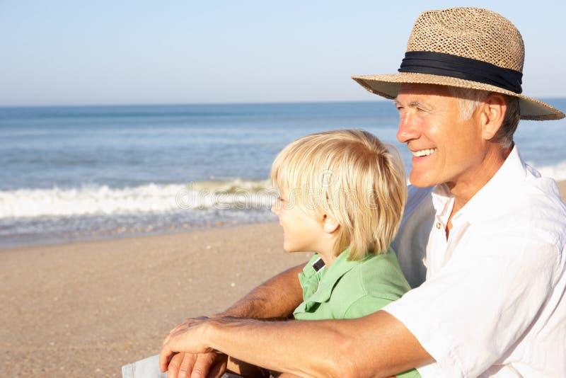 Grootvader met kind op strand stock foto