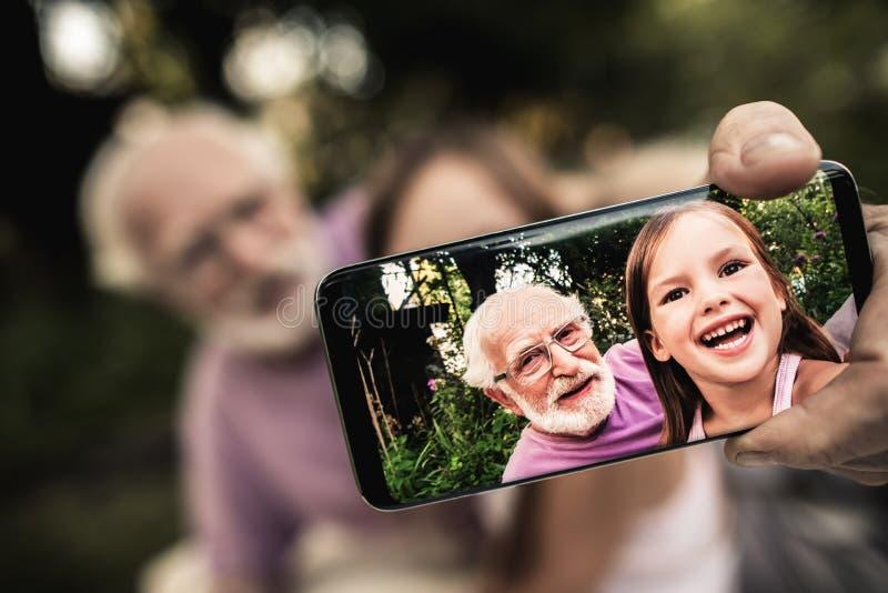 Grootvader met kleinkind die beeld van zich nemen stock afbeelding