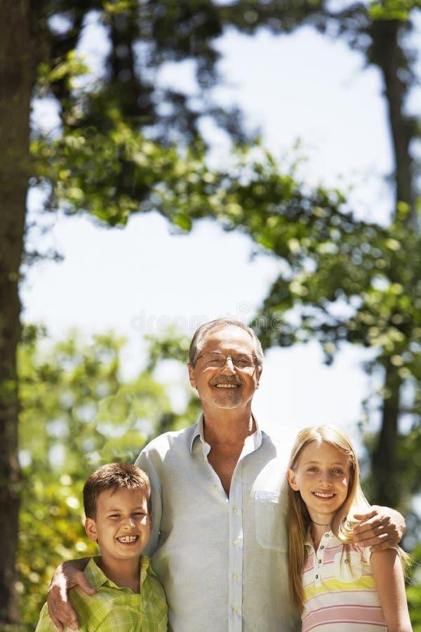 Grootvader met Kleinkinderen in Park stock foto's