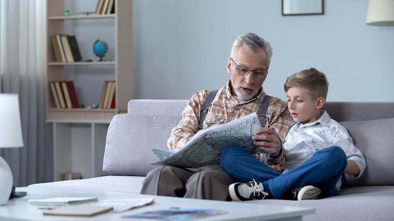 Grootvaderveteraan het bekijken kaart met kleinzoon die frontlijn tonen die oorlog herinneren royalty-vrije stock foto's