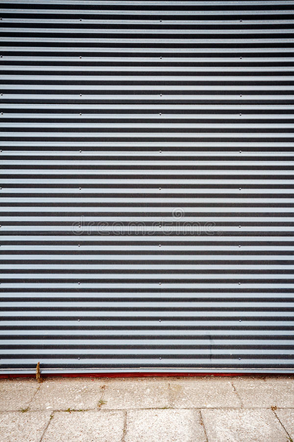 Grooved metal wall. Dark gray industrial grooved metal wall royalty free stock photography