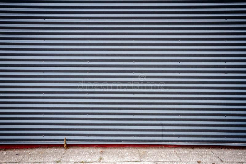 Grooved metal wall. Dark gray industrial grooved metal wall royalty free stock photos