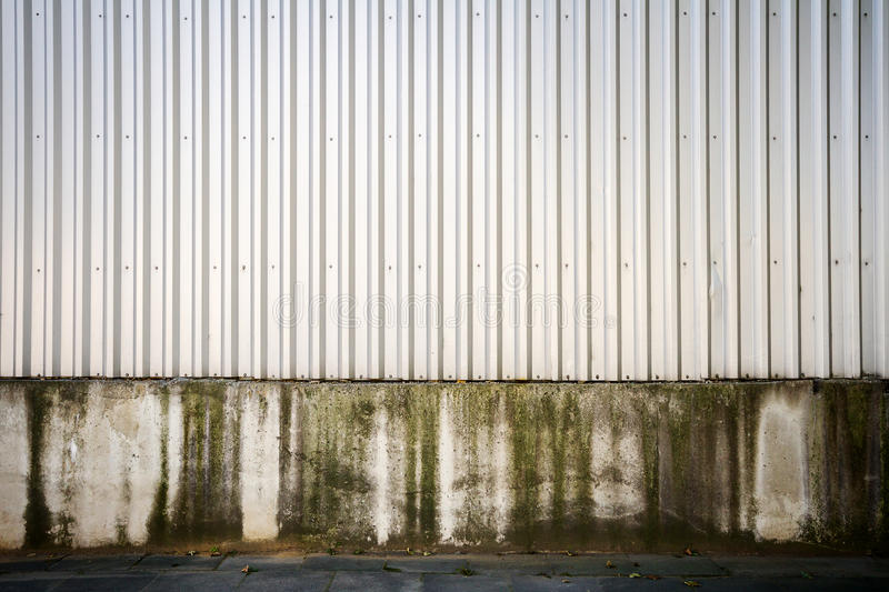 Grooved metal wall. Gray industrial grooved metal wall on concrete base royalty free stock images