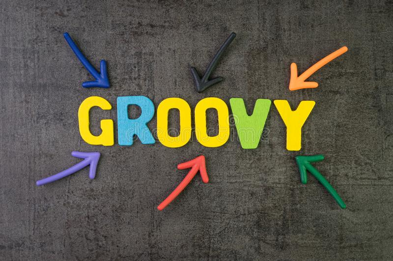 Groovy modern programming language for software development or application concept, multi color arrows pointing to the word Groovy. At the center of black stock photo