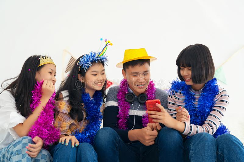 Group Girl and boy teens playing on mobile phones, hipster style, students, friends holding smartphone, after selfie stock photo