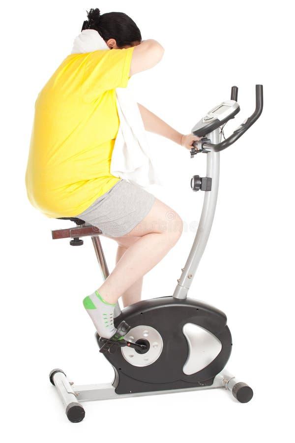 Gros femme sur la bicyclette stationnaire de forme physique photos libres de droits