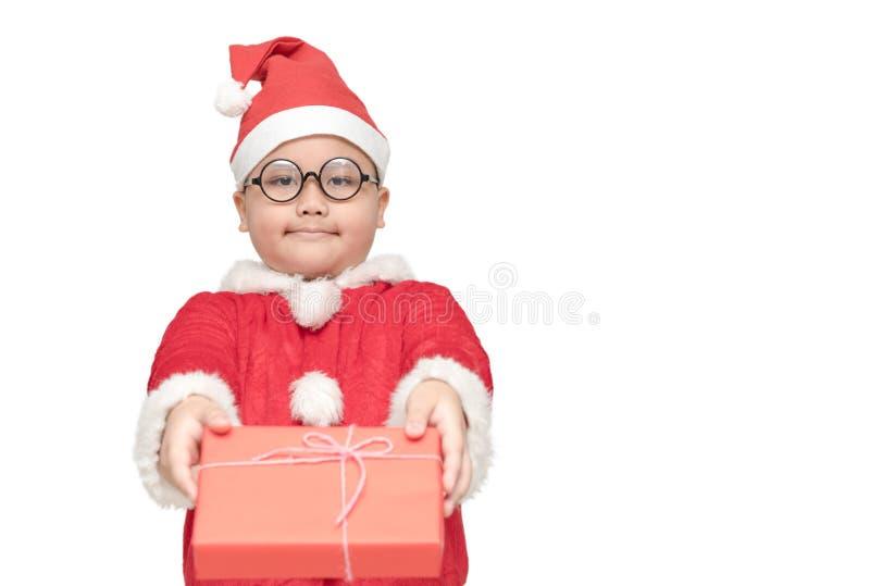 Gros garçon obèse en costume du père noël donnant le boîte-cadeau et le sourire image libre de droits