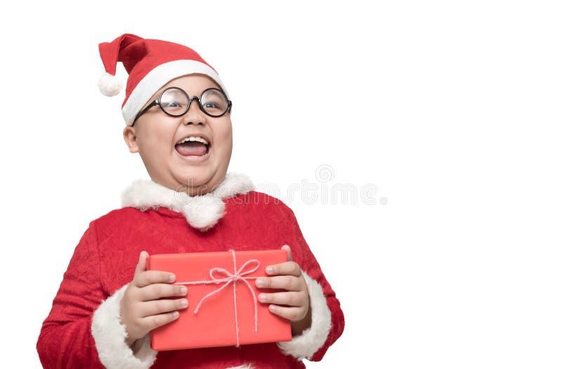 Gros garçon obèse en costume du père noël tenant le boîte-cadeau et rire images stock