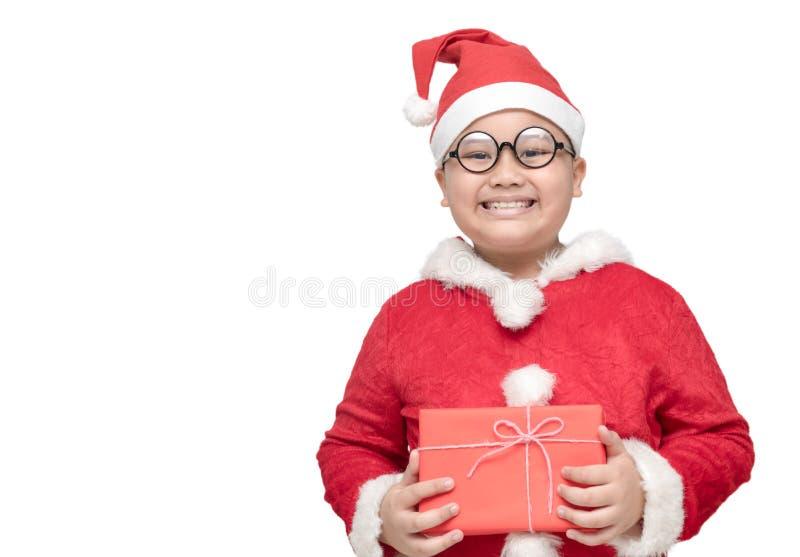 Gros garçon obèse en costume du père noël tenant le boîte-cadeau et le sourire photo stock