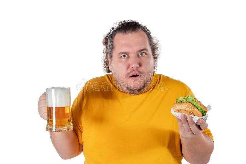 Gros hamburger mangeur d'hommes drôle et boisson potable d'alcool sur le fond blanc images stock