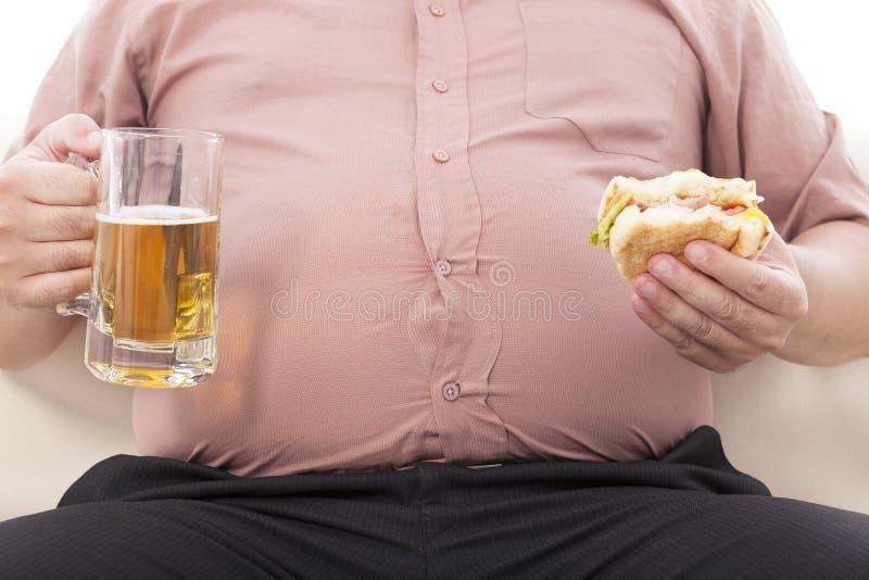 Gros homme d'affaires tenant la tasse de bière et l'hamburger photographie stock libre de droits